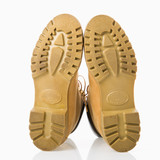 Pair of tan construction boots with sole facing viewer. poster