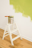 Paintbrush on can on top of step ladder with painted wall. poster