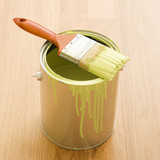 Paintbrush resting on paint can on wood floor. poster