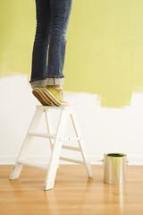 Legs of woman standing on tiptoe on stepladder.