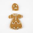 Frowning female gingerbread cookie broken in half.