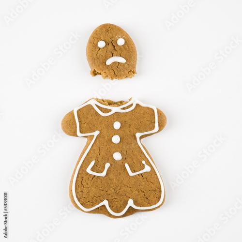 Frowning female gingerbread cookie broken in half.