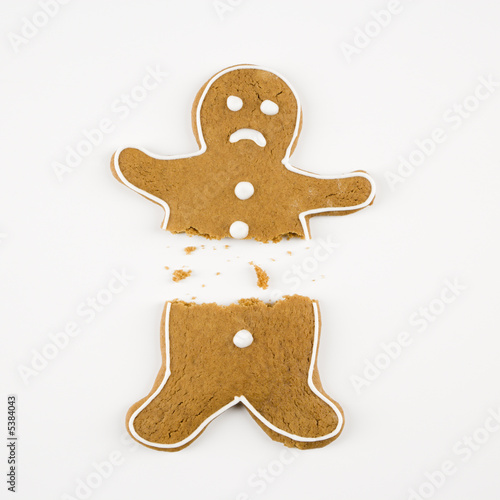 Frowning male gingerbread cookie broken in half.