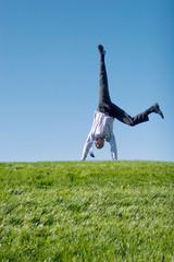 Happy businessman doing somersault on grass