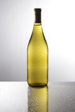 Bottle of white wine on a reflective tabletop.  poster