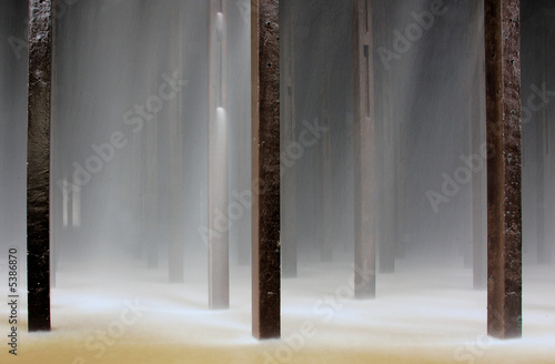 Water and poles underneath a cooling tower of a power plant