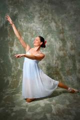 Ballerina kneeling down and raising hands.