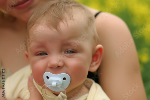 Young cute boy with soother in his mouth
