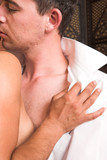 Multi-ethnic couple in passionate embrace and undressing  poster