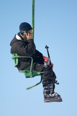 skier with mobile phone on chair lift