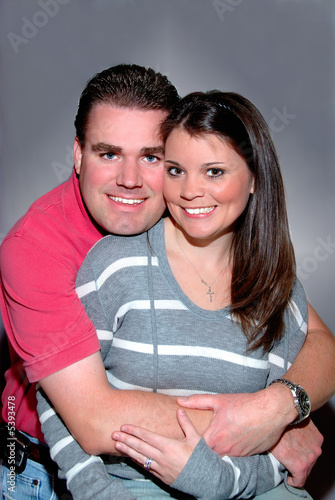 A young married couple smiling in an embrace.