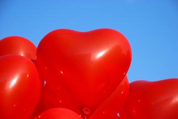 Rote Herzluftballons vor blauem Himmel