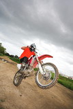 Young man riding around on his dirtbike doing tricks  poster