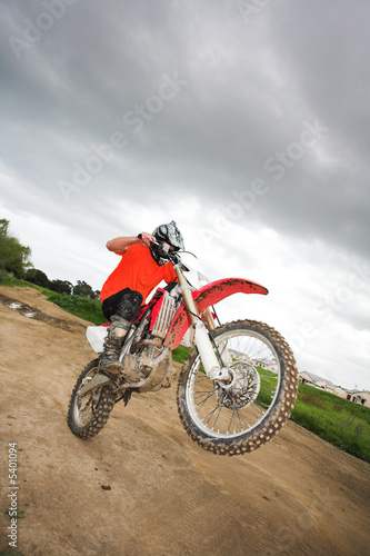 Young man riding around on his dirtbike doing tricks