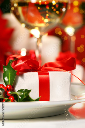 Little red ribboned gift with a sprig of holly on plate