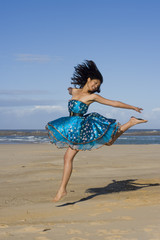 Pretty girl jumping wearing a puffy blue dress
