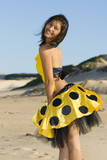 Playful girl wearing a yellow polka dot outfit