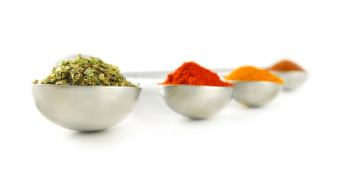 Assorted spices in metal measuring spoons on white background