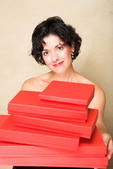 Smiling woman with short curly hair, holding a stack of red gift