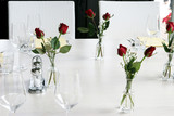 Elegant table setting with vases of red roses and white linen. poster
