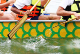 Competitors rowing tin a dragon boat race. poster