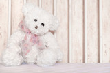 Small white teddy bear, sitting in child cot poster