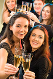 Portrait of  young women raising up their bocals of champagne