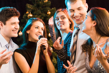 Portrait of five friends having fun at karaoke party