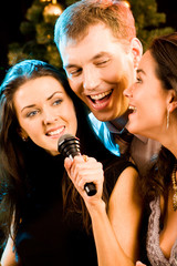 Portrait of three attractive friends singing together