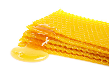 A honeycomb with honey, reflected on white background