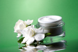 container of opened moisturizing face cream and white gardenias poster