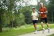 Senior couple running through the woods. Some motion blur.