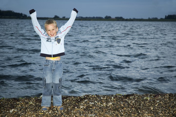Boy standing in front of a lake at night.