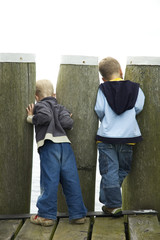 Two boys looking though a couple of poles.