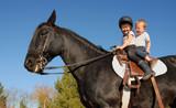 two happy children on their black stallion.. poster
