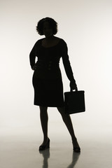 Silhouette of businesswoman holding briefcase.
