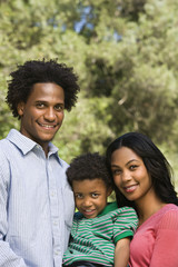 Family portrait of parents and young son smiling.