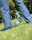 Son running and kicking ball towards father in park. poster