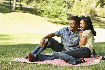 Portrait of smiling couple in park sitting on picnic blanket.