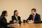 Businesspeople sitting at conference table talking and smiling. poster