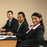 Businesspeople sitting at conference table smiling. poster