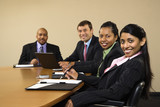 Businesspeople sitting in conference smiling. poster