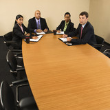 Businesspeople sitting at conference table. poster