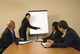 Businesspeople sitting at conference table during presentation. poster