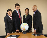 Corporate businesspeople standing around globe smiling. poster
