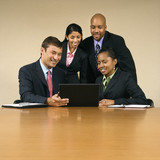 Businesspeople gathered around laptop smiling. poster