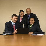 Businesspeople gathered around laptop computer smiling. poster
