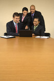 Businesspeople gathered around laptop looking and smiling. poster