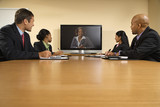 Businesspeople in conference looking at flat screen display. poster