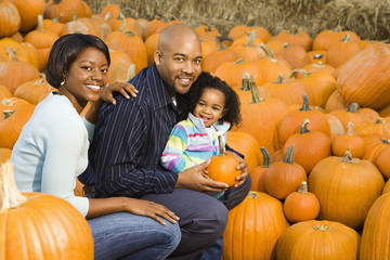 Happy family picking out pumpkin and smiling for fall portrait.